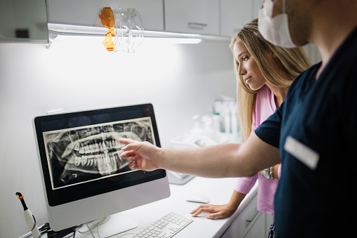 A dental hygienist helping patient look at her digital x-rays at Turella Oral Surgery.