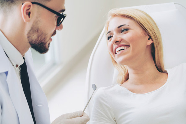 Woman smiling while oral surgeon talks